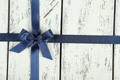 Blue Ribbon con el arco en el fondo de madera blanco Foto de archivo libre de regalías