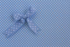 Blue ribbon on polka dots. Blue ribbon with polka dots on the same background. Minimalistic style. Flat lat. Text space royalty free stock photo