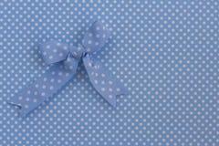 Blue ribbon on polka dots. Royalty Free Stock Photo