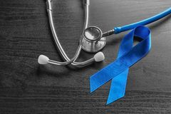 Blue ribbon and stethoscope on wooden background. Cancer awareness concept royalty free stock photo