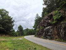 Mountain Road by Rock Wall. The Blue Ridge Parkway outside Asheville, North Carolina with large rocks, trees, grass, and clouds Royalty Free Stock Photos