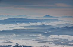 Blue ridges, misty snowy valleys and a conical peak in Slovakia. Elevated view of sunny winter scenery with blue mountain ridges, misty valleys and cone shaped royalty free stock images