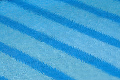 Blue Riippling water. Water rippling in a swimming pool with blue striped lanes Stock Images