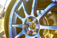 Blue rims with golden bolts on a black reflective car and sun bu Stock Image