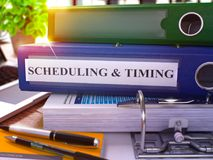 Blue Ring Binder with Inscription Scheduling and Timing. 3d. Blue Ring Binder with Inscription Scheduling and Timing on Background of Working Table with Office Stock Photography