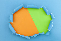 Blue ripped open paper on green and orange paper background. Stock Photography