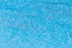 Blue ripped water in swimming pool with sunny reflections. For background design royalty free stock photography