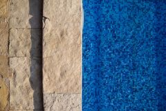 Blue ripped water in swimming pool in tropical resort with edge of pavement. Part of Swimming pool bottom background. royalty free stock images