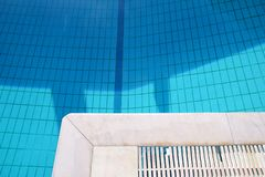 Blue ripped water in swimming pool in tropical resort with edge of pavement. Part of Swimming pool bottom background. royalty free stock photos