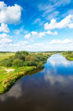 Blue river, cloud sky, green shores Stock Images