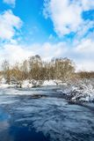 The blue river is covered with a thin transparent layer of ice, on the banks and trees there is white snow, a winter landscape. In the daytime royalty free stock photo