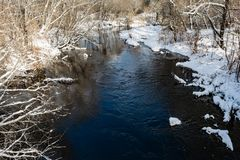 The blue river is covered with a thin transparent layer of ice, on the banks and trees there is white snow, a winter landscape. In the daytime stock photography