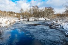 The blue river is covered with a thin transparent layer of ice, on the banks and trees there is white snow, a winter landscape. In the daytime royalty free stock image