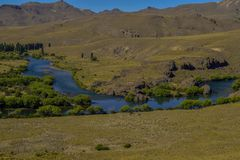 A blue river crosses the desolate Patagonian landscape stock images
