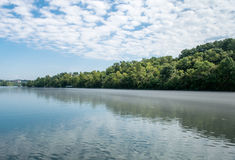 Blue river reflecting sky and trees Stock Photos