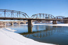Blue river reflections in the City of Bridges. A view of the Victoria Bridge and Broadway Bridge in Saskatoon, Canada on a sunny day in winter royalty free stock image