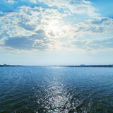 Blue river with sun in clouds Royalty Free Stock Photography