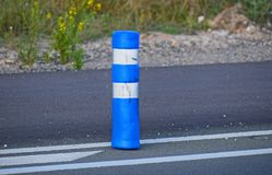 A Blue Road Bollard. A modern shaped traffic come next to the road Royalty Free Stock Photos