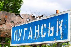 Blue road sign with the inscription in Ukrainian Lugansk, punched by bullets during the war in the Donbass, conflict East Ukraine. Destruction royalty free stock photo