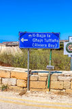 Traffic sign - Malta. Blue road sign showing the way to the one of the best Malta's beaches - Ghajn Tuffieha, Malta Royalty Free Stock Photo