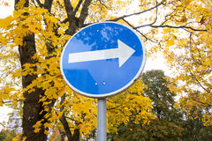 Blue road sign with white arrow pointing right Stock Photography