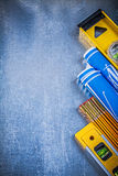 Blue rolled blueprints levels yellow wooden meter on metallic su Royalty Free Stock Photo