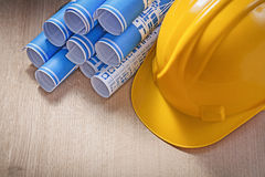 Blue rolled construction plans hard hat on wooden board maintena Stock Photography