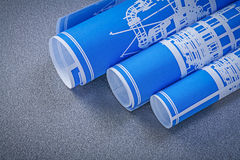 Blue rolled up blueprints on grey surface construction concept Royalty Free Stock Photography