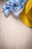 Blue rolled up construction plans hard hat on wooden board copy Royalty Free Stock Images