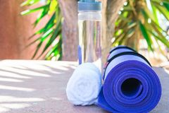 Blue Rolled Yoga Mat Bottle with Water White Towel on Greenery Palm Tree Nature Background. Sunlight. Relaxation Summer Meditation. Blue Rolled Yoga Mat Bottle stock images