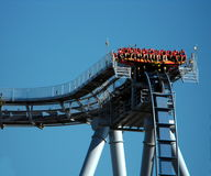 Blue Roller Coaster With People. Blue twisted roller coaster track with beam support. People suspended Stock Photography