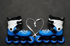 Blue roller skates and heart from laces on dark chalk board background. Valentine`s day. Blue roller skates and heart from laces on dark chalk board background Stock Photography