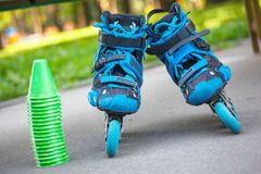 Blue roller skates with slalom cones lying on asphalt. Royalty Free Stock Images