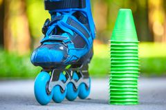 Blue roller skates with slalom cones lying on asphalt. Stock Image