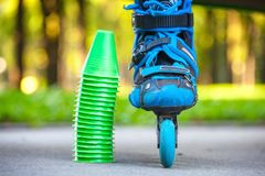 Blue roller skates with slalom cones lying on asphalt. Royalty Free Stock Photo