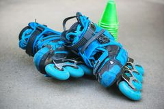 Blue roller skates with slalom cones lying on asphalt. Royalty Free Stock Image