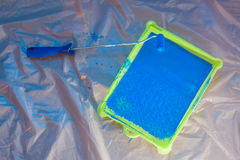 Blue rolling brush with green pallet. Blue rolling brush and green pallet with blue paint on pollythene stock images