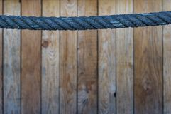Blue rope as a handrail in the upper third. Wooden wall in the b. Ackground with selective sharpness royalty free stock images