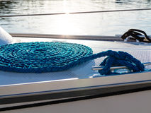 Blue rope coiled on dock and tied to metal cleat. Royalty Free Stock Photos