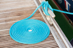 Blue rope coiled on a wooden dock Royalty Free Stock Images