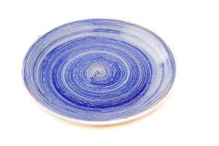Blue round ceramic plate with spiral pattern, isolated on white. Blue round ceramic plate with spiral pattern, isolated on the white Royalty Free Stock Image