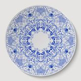 Blue round floral ornament applied to the ceramic plate. Stock Image