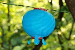 Blue round lantern on Buddha's birthday on a blurry floral green background royalty free stock photos