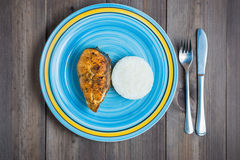 Blue round plate with red fish, rice, fork and knife on dark wooden background. Blue turquoise round plate with red fried fish, rice, fork and knife on dark Stock Photos