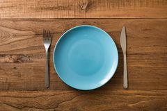 Blue Plate on brown wooden background with utensils Stock Images