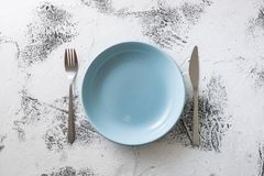 Blue Plate on white wooden background with utensils Stock Photo