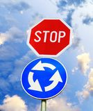 Blue roundabout crossroad road traffic sign with STOP sign against sky. Blue roundabout crossroad road traffic sign with STOP sign against blue cloudy sky Royalty Free Stock Images
