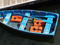 Blue row boat with orange life vests at dock Stock Images
