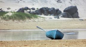 Waiting Blue Oars. A blue rowboat on the beach with the oars sticking out Stock Images