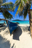 Blue rowboat and palm leaves cast shadows on sand on beautiful island in the Caribbean Sea Stock Images